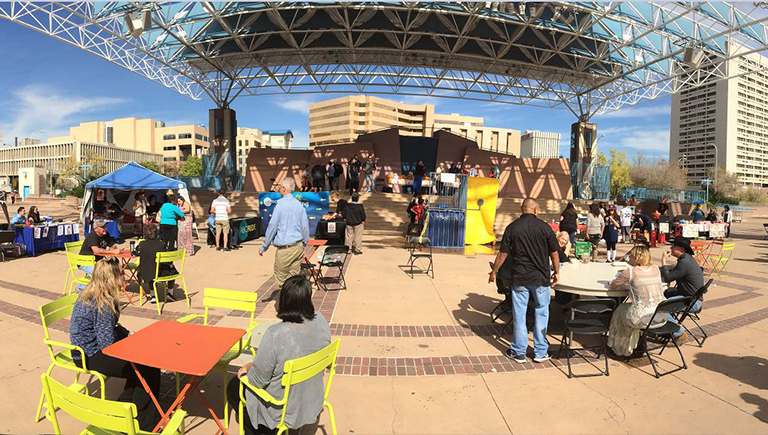 A gathering on Civic Plaza with multiple folding tables and chairs occupied with people chatting.