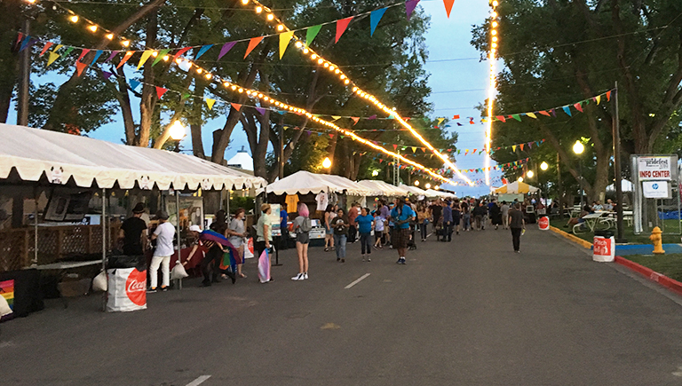 A group of people at the state fair, browsing shops along a concrete road lined with trees and decorated with strands of lights and colorful flags.