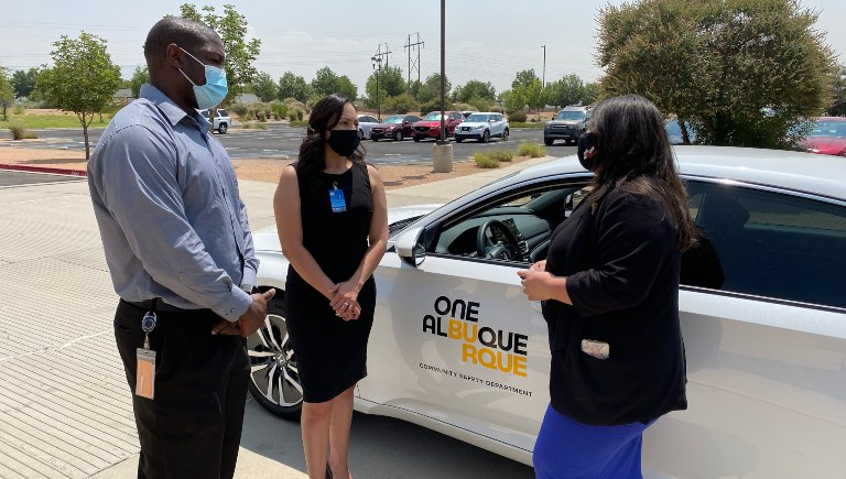 Three ACS staff members talking in front of a parked ACS vehicle.