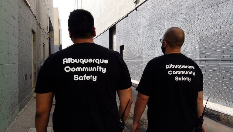 Two ACS staff members with walkie talkies wearing ACS t-shirts walking down an alley