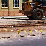 Photo of a construction vehicle near a city street covered in dirt.