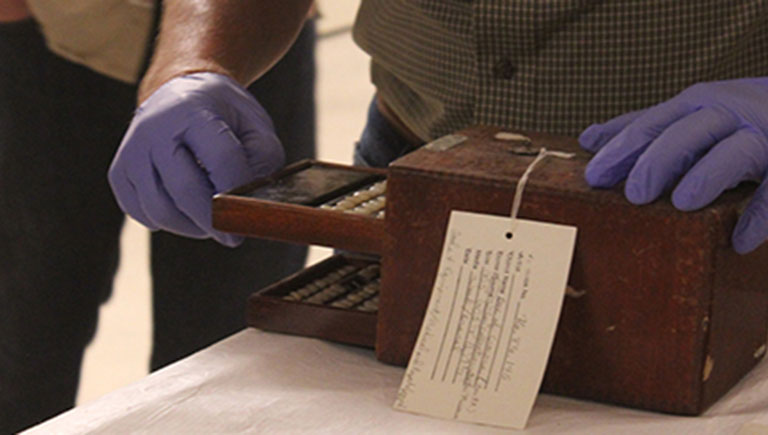 A photo of a collection piece being examined by the gloved hands of a museum staff member.