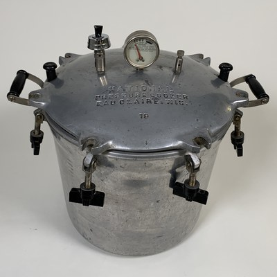 Recent History Acquisitions, April 2021. National Pressure Cooker Company, Pressure Cooker, heavy aluminum cast with brass rods and bakelite handles and thumbnuts, Albuquerque Museum, gift of Kate Padilla