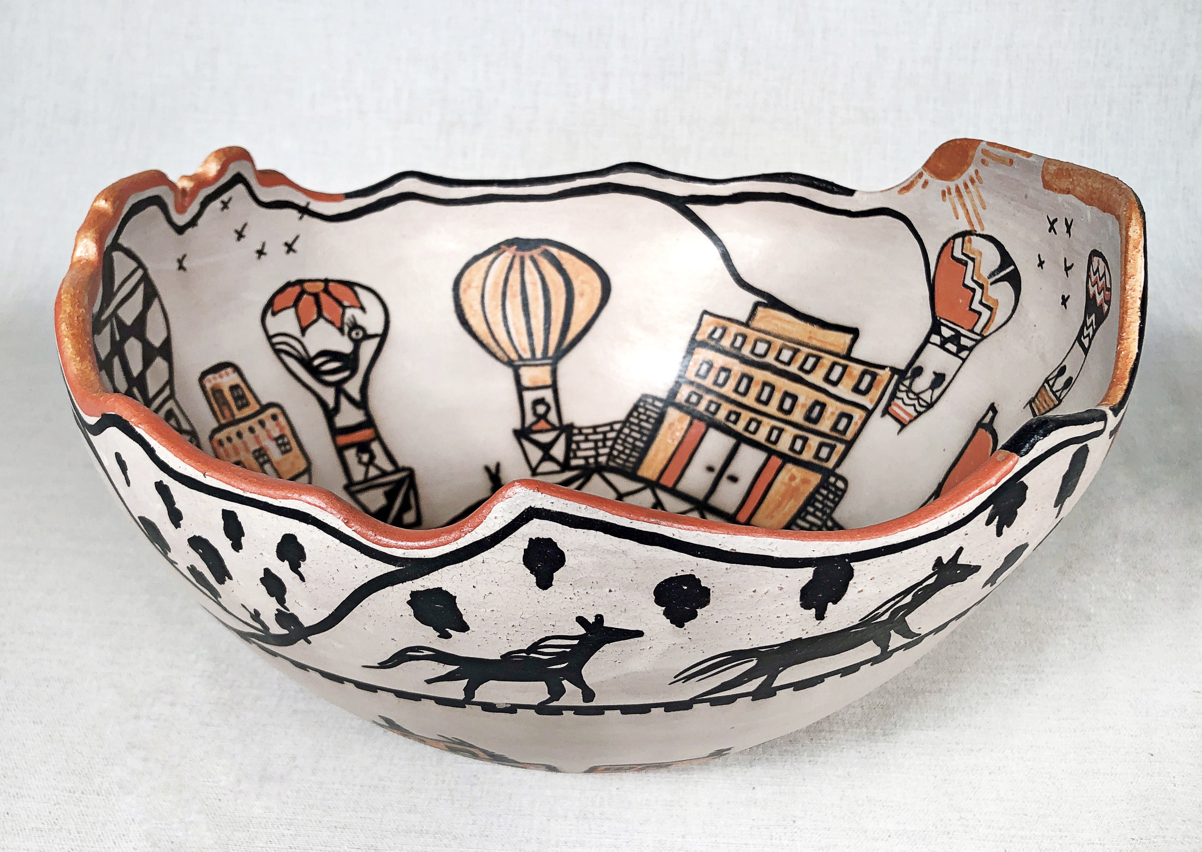 A large ceramic bowl with drawings of balloons and the Sandia Pueblo