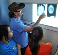 caption:A group of Camp BioPark students look at an animal x-ray.