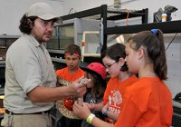 caption:A group of Camp BioPark students meet with a reptile keeper.