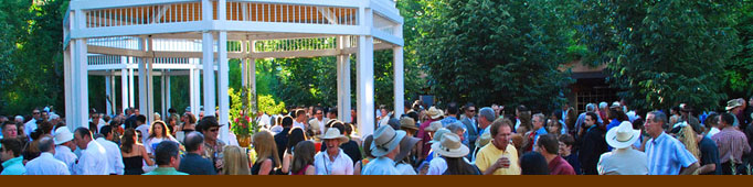 A crowd enjoys an event at the Zoo with gazebo in background.