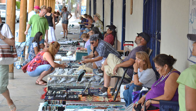 People shopping from artisans at the Old Town Portal Market.