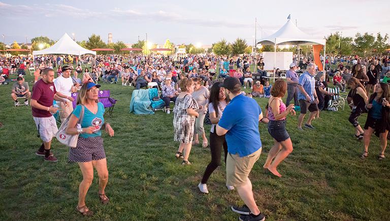Families dancing in a park at Albuquerque Summerfest.