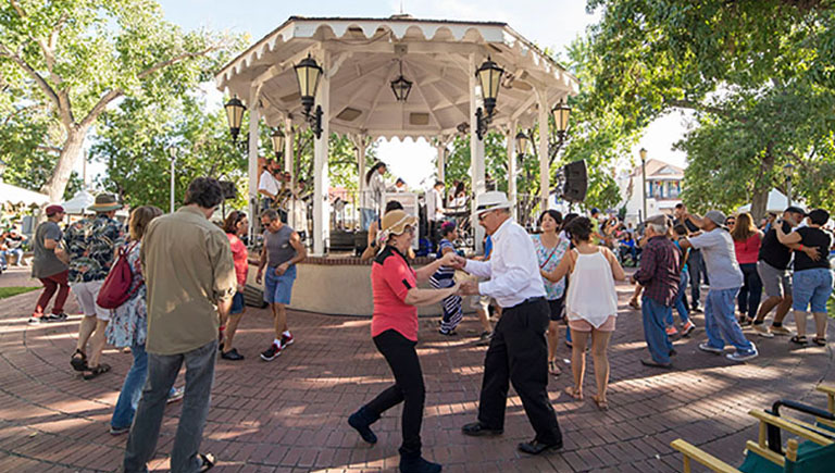 A crowd dancing to live music around the gazebo in History Old Town.