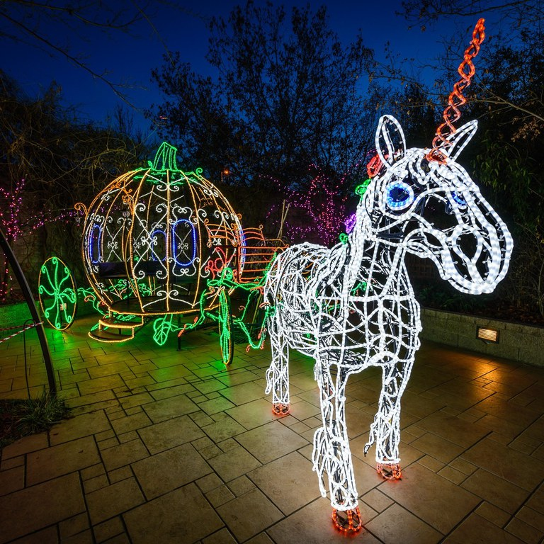 A carriage pulled by a unicorn made out of multicolored lights at the Botanic Gardens.