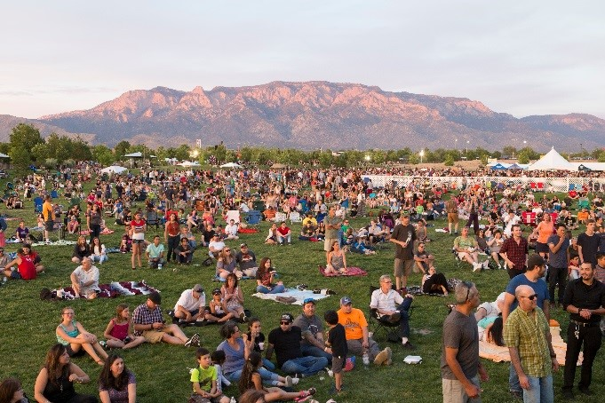 A photo of a concert with people on the grass with the Sandias in the background