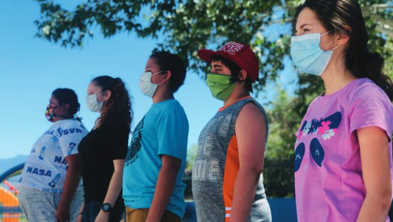 5 outh members standing in a line wearing masks