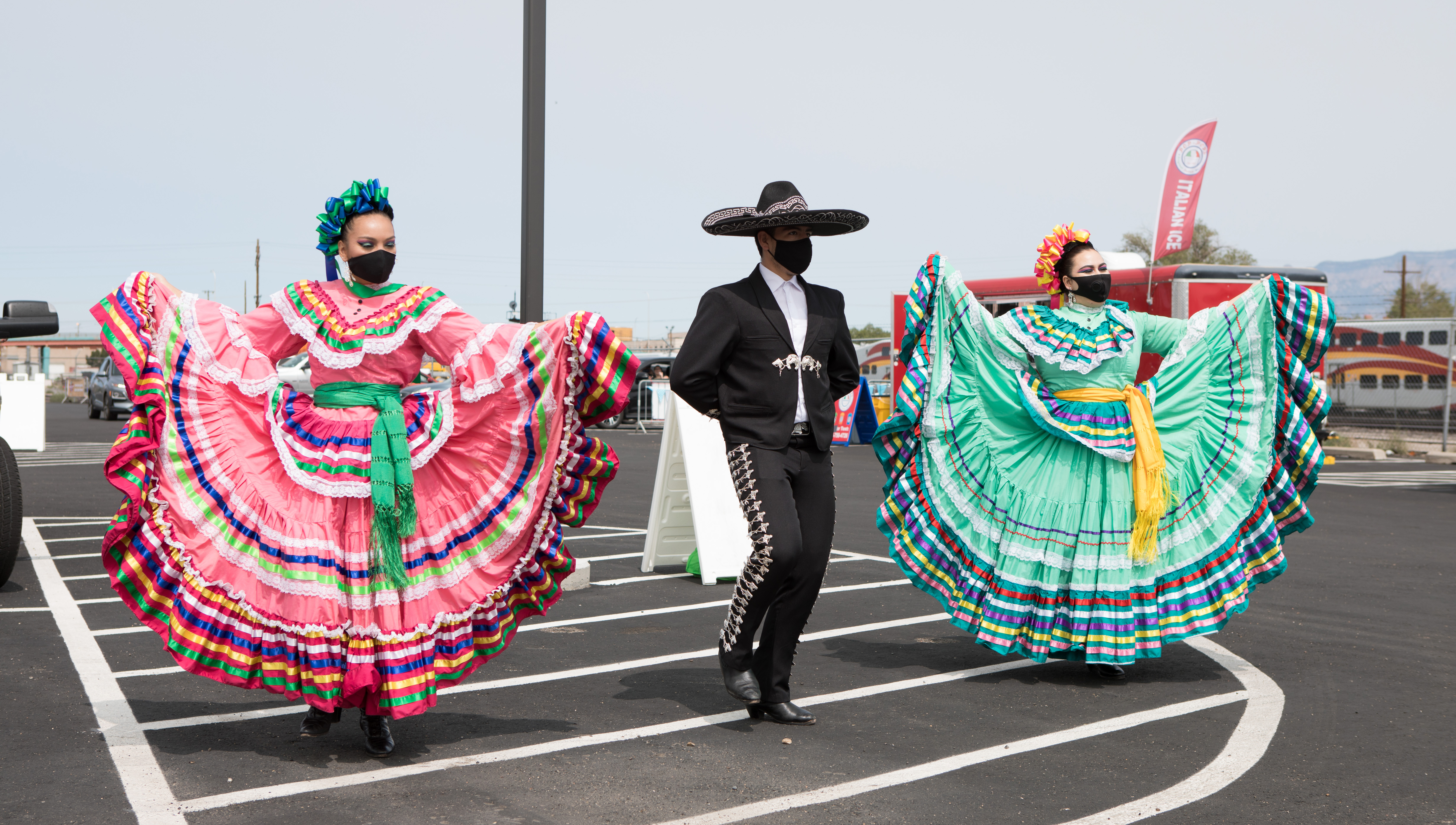 Mariachi dancers performing in a parking lot.