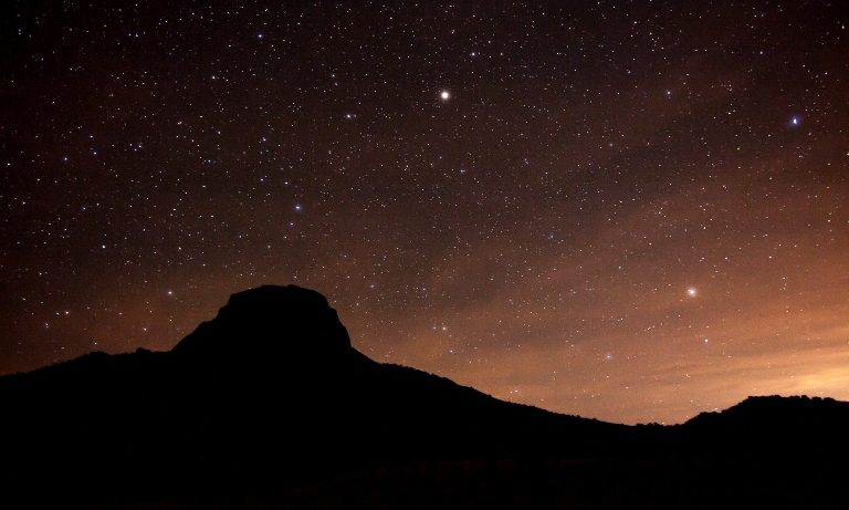 A mesa at sunset with stars above.