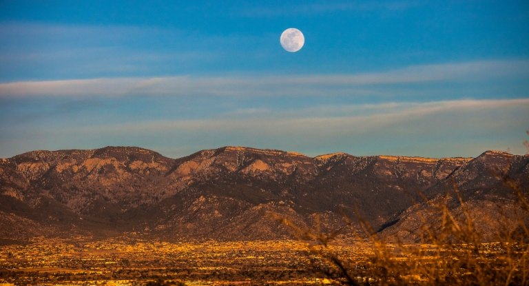 A photo of a moonrise over the Sandias.