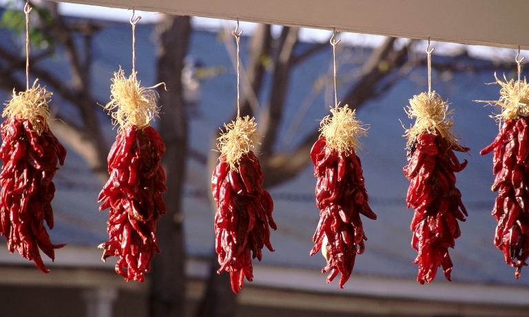 Six red chile ristras hanging on a portal