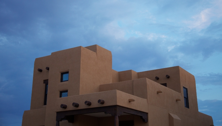 A photo of a stucco building with a blue sky behind it.