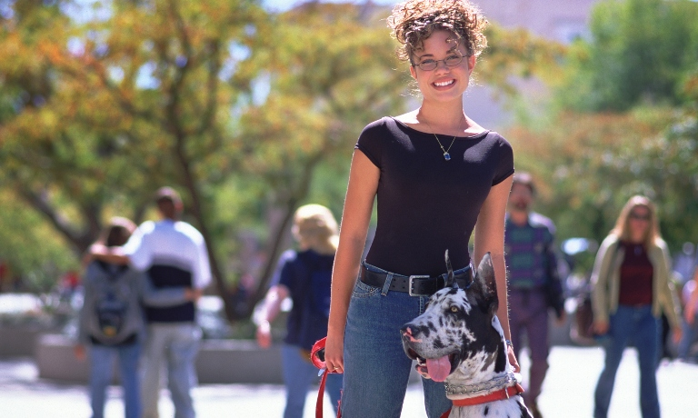 A photo of a woman with a dog on campus.