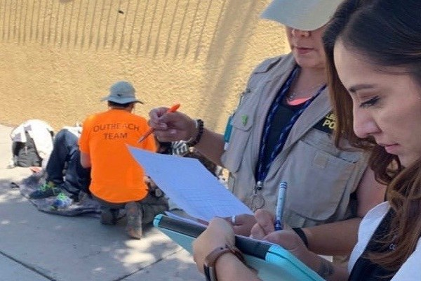 Two women taking notes as an outreach team member speaks with a homeless individual.