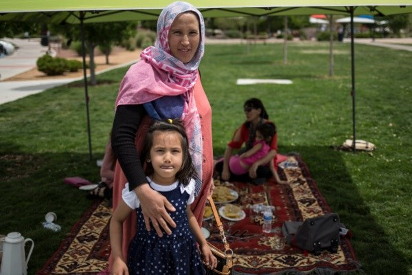 A mother and her daughter standing in front of a tent as a woman eats lunch on a carpet in the shade.