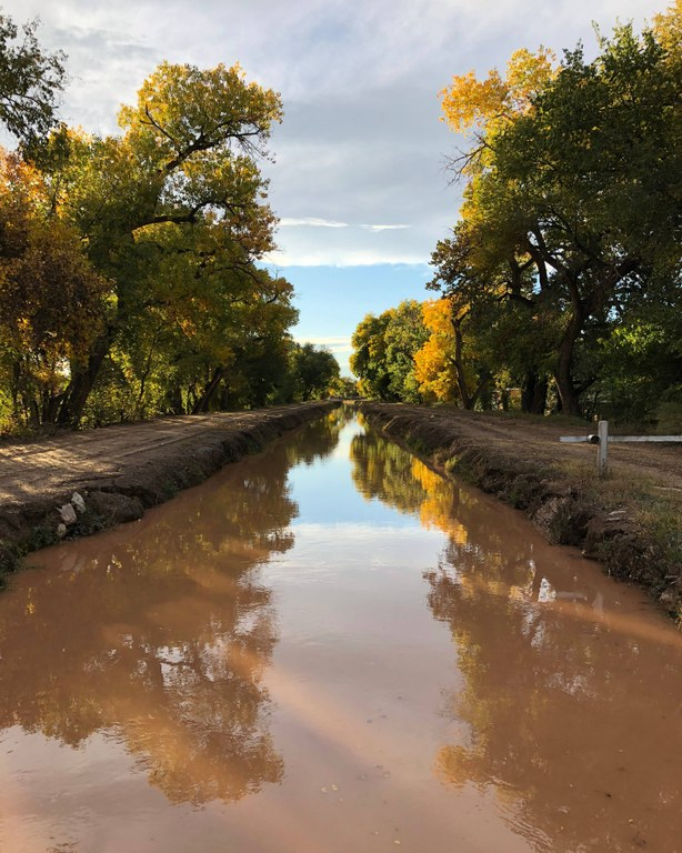 An acequia full of water.