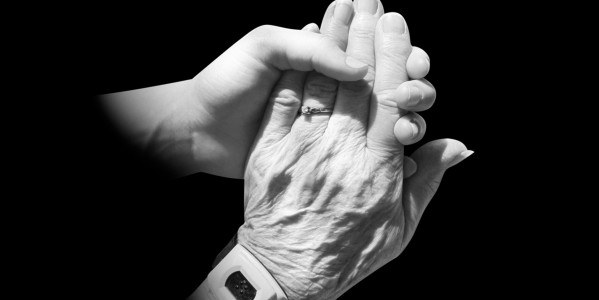 Young hand holding an elderly hand