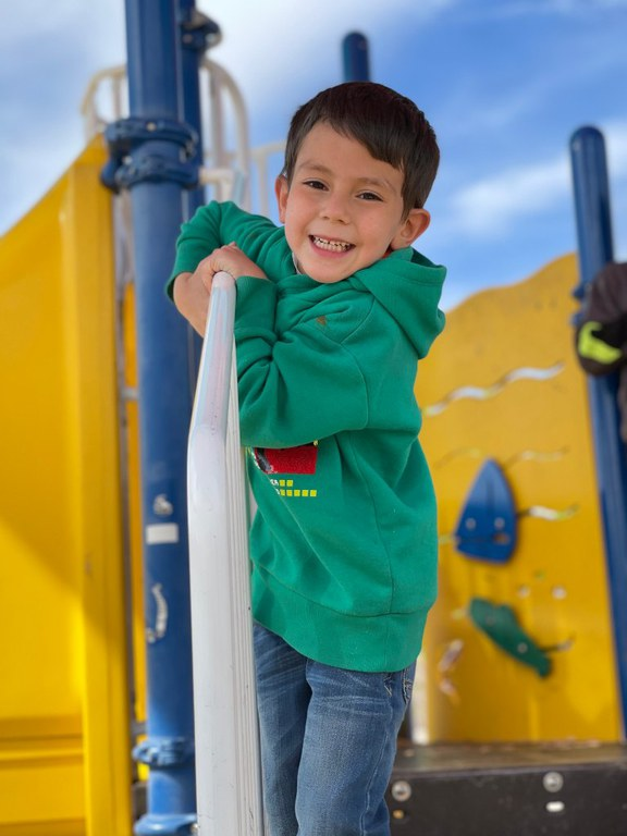 A smiling boy standing on some playground equipment.