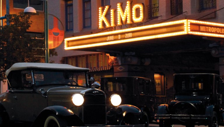 The KiMo Theatre at night with vintage vehicles outside.