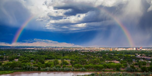 Albuquerque's horizon facing east with rainbow overhead.