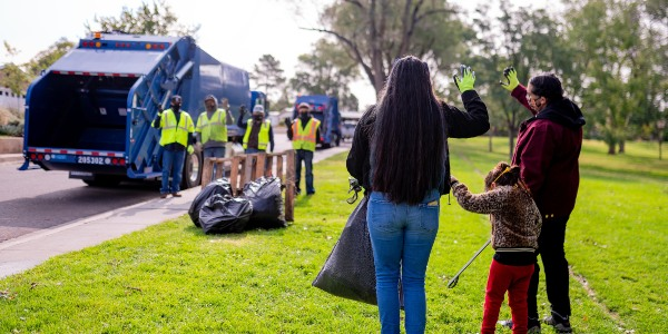 A family waiving at City of Albuquerque Solid Waste Department employees