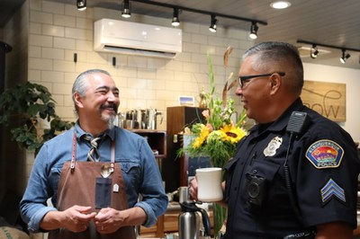 A police officer in uniform drinking coffee with a coffee shop worker.