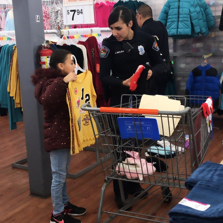 An APD Officer shopping for clothes with a young girl