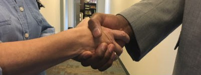 A photo of two people shaking hands.