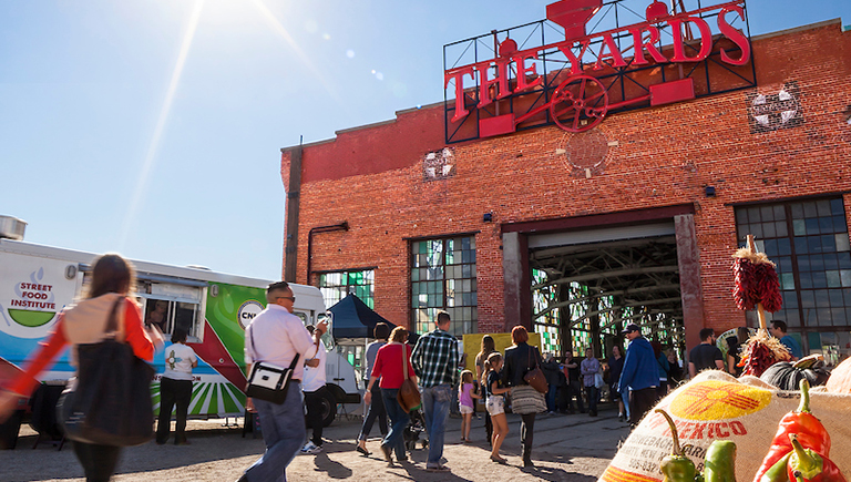 Photo of people walking into the Railyards Market entrance on a sunny day in Albuquerque, New Mexico.