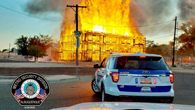 A metro security division vehicle parked in front of a burning building.
