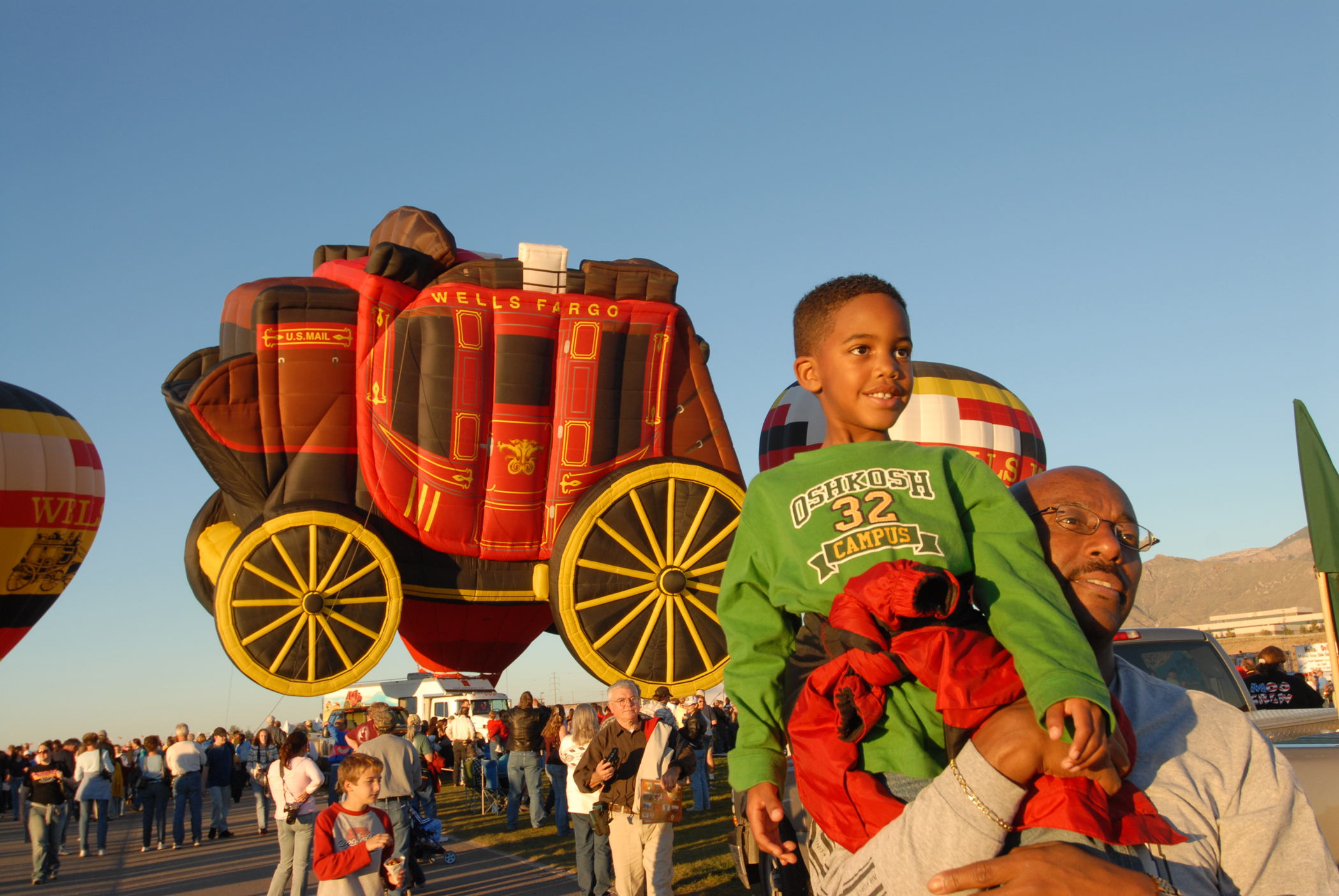 An African American father holding up his young son during Albuquerque International Balloon Fiesta