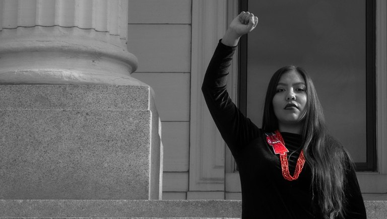 A native woman holding her fist up on the steps of a capitol building.