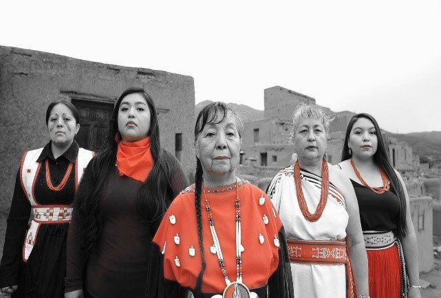 Five women in traditional native clothing standing in a line in front of an adobe building.