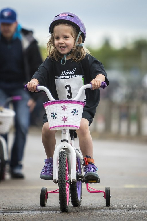 A young girl riding on a bicycle during a bike race.