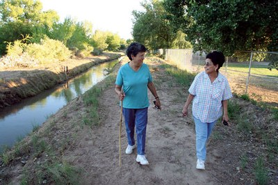Two women walking near the ditch