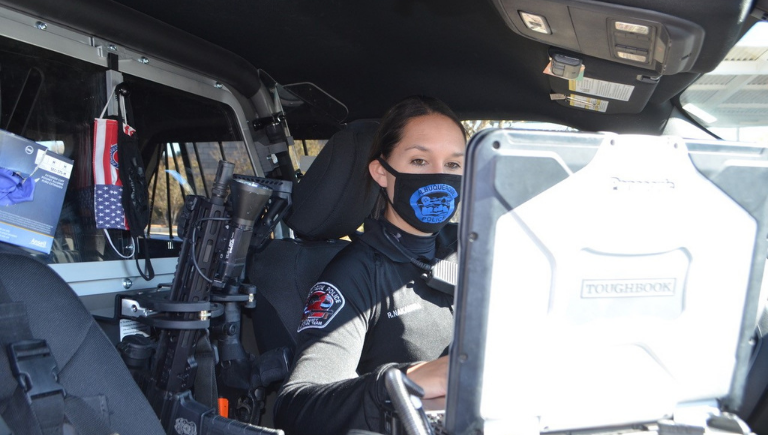 Female officer in her unit on her laptop