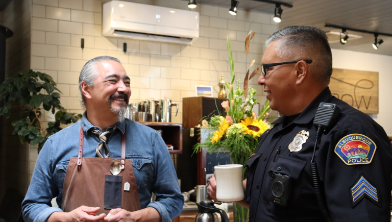 Officer at coffee with a cop event talking to community member