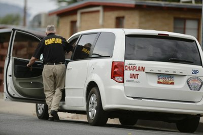 A jpg of an APD Chaplain getting into van.