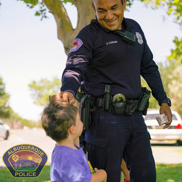 An Albuquerque Police Officer handing a sticker to a young child