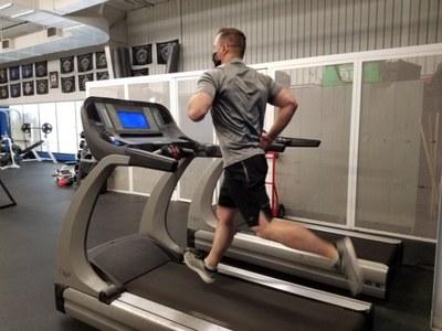 A jpg of an APD officer running on a treadmill at a gym.