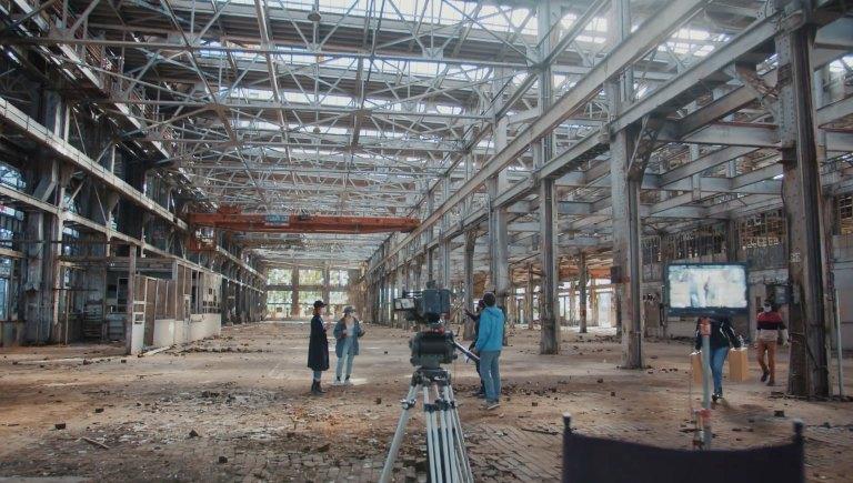 A camera crew filming a scene inside the rail yards.
