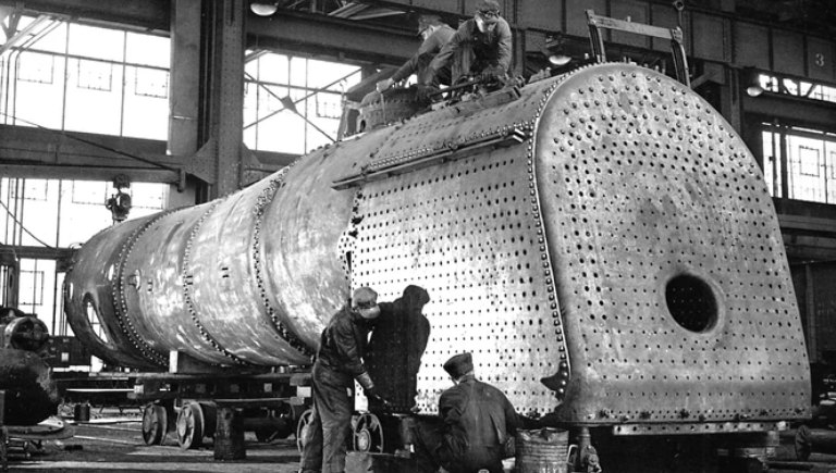 A historic image of rail yard workers conducting maintenance on an engine.
