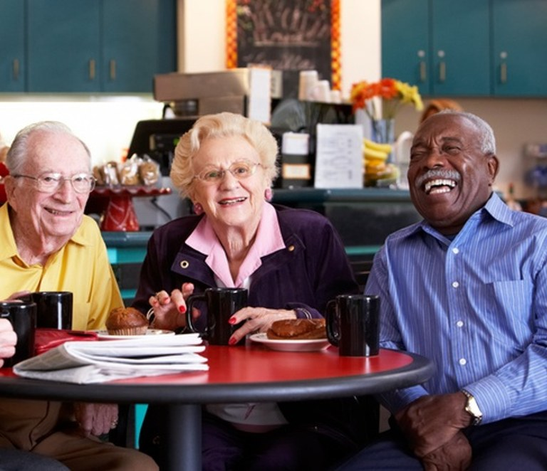 Three people sitting at a table laughing