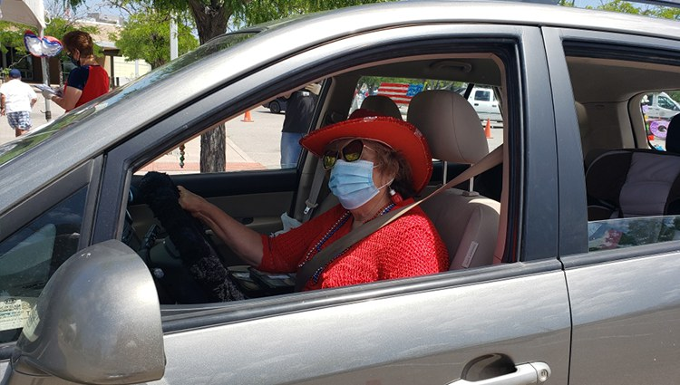 Senior Woman Wearing a Mask in a Parked Car